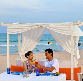 A couple enjoying romantic private dining by the beach